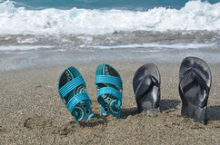 Two pairs of flip-flops on the beach, tropical vacation concept.  Stock Photo