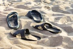 Two pairs of flip-flops on the embossed beach sand, beach in the summer evening time. Two pairs of flip-flops on the embossed beach sand, the beach in the summer stock photo