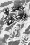 Two pairs of flip-flops on the embossed beach sand, beach in the summer evening time. Two pairs of flip-flops on the embossed beach sand, the beach in the summer stock photography