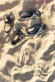 Two pairs of flip-flops on the embossed beach sand, beach in the summer evening time. Two pairs of flip-flops on the embossed beach sand, the beach in the summer stock images