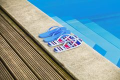 Two pairs of flip flops by the pool. In summer day stock image