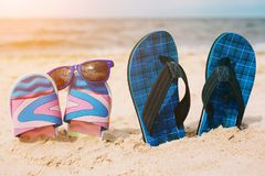 Two pairs of flip-flops in sand on beach. Sunglasses on one of them. Summer vacation concept. Sea shore. Paradise. stock photo