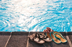Two pairs of flip-flops by swimming pool. Two pairs (men's and woman's) of flip-flops by swimming pool with sunlight reflections Stock Photos