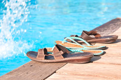Two pairs of flip-flops by the swimming pool Royalty Free Stock Photo