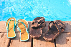 Two pairs of flip-flops by swimming pool. Two pairs (men's and woman's) of flip-flops by swimming pool with sunlight reflections Royalty Free Stock Photography