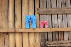 Two pairs of flip flops on a wooden wall waiting for summer vacation stock photos