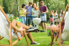 Two pairs of friends. Spend their free time in the fresh air drinking and eating grilled food Royalty Free Stock Images