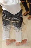 Two pairs of girls legs - barefoot and in flip-flops in white and black dress for the eastern belly dance Stock Images