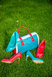 Two pairs of green and red shoes and bag lay on the grass Royalty Free Stock Images