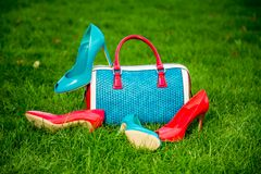 Two pairs of green and red shoes and bag lay on the grass Stock Photo