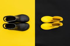 Two pairs of gumboots - yellow female and black male - standing opposite to each other on the inverse backgrounds. Top view, copy space.Colorful and vivid royalty free stock photo