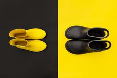 Two pairs of gumboots - yellow female and black male - standing opposite to each other on the inverse backgrounds. Top view. The concept of He and She stock images