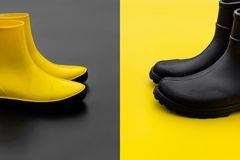 Two pairs of gumboots - yellow female and black male - standing opposite to each other on the inverse backgrounds. Women`s yellow rubber boots on a black stock image
