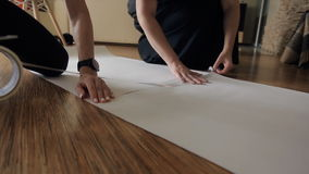 Two pairs of hands connect sheets and fasten them with tape. On a wooden laminate there are two sheets of paper A3, on both sides of them sitting women in stock footage