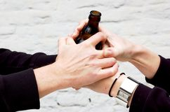 Two pairs of hands holding a dark glass Royalty Free Stock Photo
