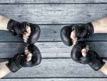 Two pairs of human hands in black leather boxing gloves facing e Royalty Free Stock Photos