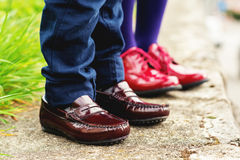 Two pairs of kids feet wearing fashion shoes Royalty Free Stock Images