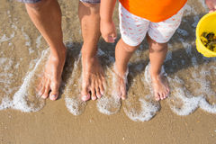 Two pairs of legs adult and child washed waves of the sea Stock Images