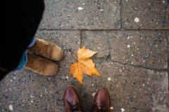 Two pairs of legs and autumn leaf Royalty Free Stock Photos