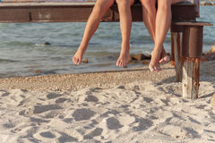 Two pairs of legs dangling over the beach sand.  royalty free stock photography