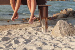 two pairs of legs dangling over the beach sand royalty free stock photo