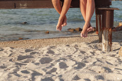two pairs of legs dangling over the beach sand stock images
