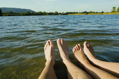 Two pairs of legs in a lake. Stock Photography