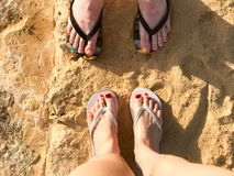 Two pairs of legs male and female with a beautiful pedicure in black and white flip-flops  on the sea in a tropical resort on sand. Y stones on the beach and Royalty Free Stock Photo