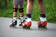 Two pairs of legs on roller skates Stock Image