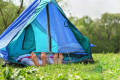 Two pairs of legs stick out from tent Royalty Free Stock Image