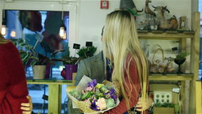 Two pairs of lovers kissing in the store. Girls are holding flowers in hands sitting on the knees of the guys. One lonely man sitting on a chair with cactus in stock video footage