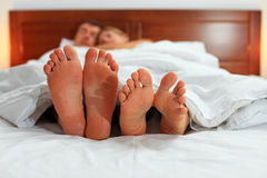 Two pairs of male and female feet. Seen from under the blanket Royalty Free Stock Photo