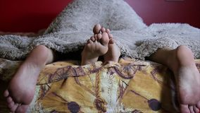 Two pairs of male and female feet seen from under the blanket. sleep together, lovers having sex. couple in a intimal stock footage