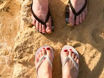 Two pairs of male and female legs with a manicure in slippers, a foot with fingers in flip-flops on a stone sandy floor, earth, be. Ach in a tropical warm hot Royalty Free Stock Photo