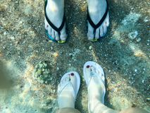 Two pairs of male and female legs in slippers, feet with fingers in flip-flops under the water, underwater view of the sea, the oc. Ean in a tropical resort on stock images