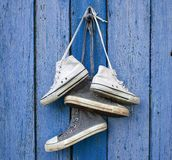 Two pairs of old worn textile sneakers hang on a nail. Two pairs of very old worn textile sneakers hang on a nail, old blue wooden background stock photography