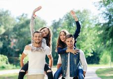 Two pairs of young people in park, girls are waving Stock Image