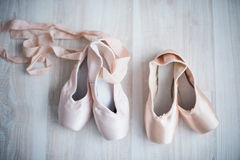 Two pairs of pointe shoe on the wooden floor Royalty Free Stock Photography
