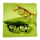 Two pairs of retro eyeglasses on creative support. Retro eyeglasses with black frame and yellow frame on creative support made of green paper, photographed on Stock Image