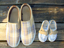 Two pairs of shoes. One big and one small pair of shoes on wooden flooring Royalty Free Stock Photography