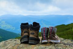 Two pairs of shoes - clean and dirty in mud stay on the rock. Royalty Free Stock Images