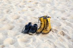 Two pairs of shoes on the sand. Two pairs of shoes on the sand, sneakers and boots Stock Images
