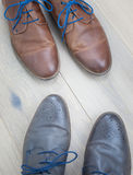 Two pairs of shoes toe to toe on  a wooden floor Royalty Free Stock Photography
