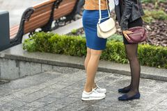 Two pairs of slim girls legs in short skirts, white leather sneakers and comfortable summer shoes on low platform. Fashion, style. And modern design concept stock photos