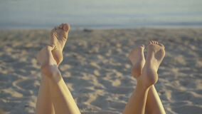 Two pairs of slim young female feet at the background of sandy beach and water. Unrecognizable Caucasian tanned women