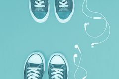 Two pairs of sneakers with mobile headphones stock photo