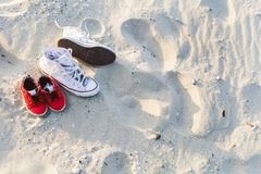 Two pairs of sneakers. Two pairs of gumshoes, mom and son, red and white, stand on the sand at a sunset beach Royalty Free Stock Photos