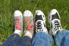 Two pairs of sneakers. Two pairs of women& x27;s and men& x27;s sneakers on a background of green grass Royalty Free Stock Photos
