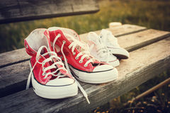 Two pairs of sports shoes on a bench at sunset Stock Photos