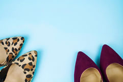Two pairs of stiletto shoes in different colors and patterns on light blue background. Stock Images